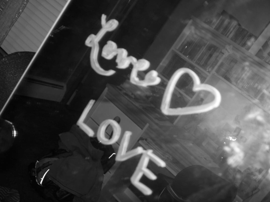 """The word """"love"""" is written twice on a mirror with lipstick. A desk full of books is subtly reflected in the background. The photo is black and white."""