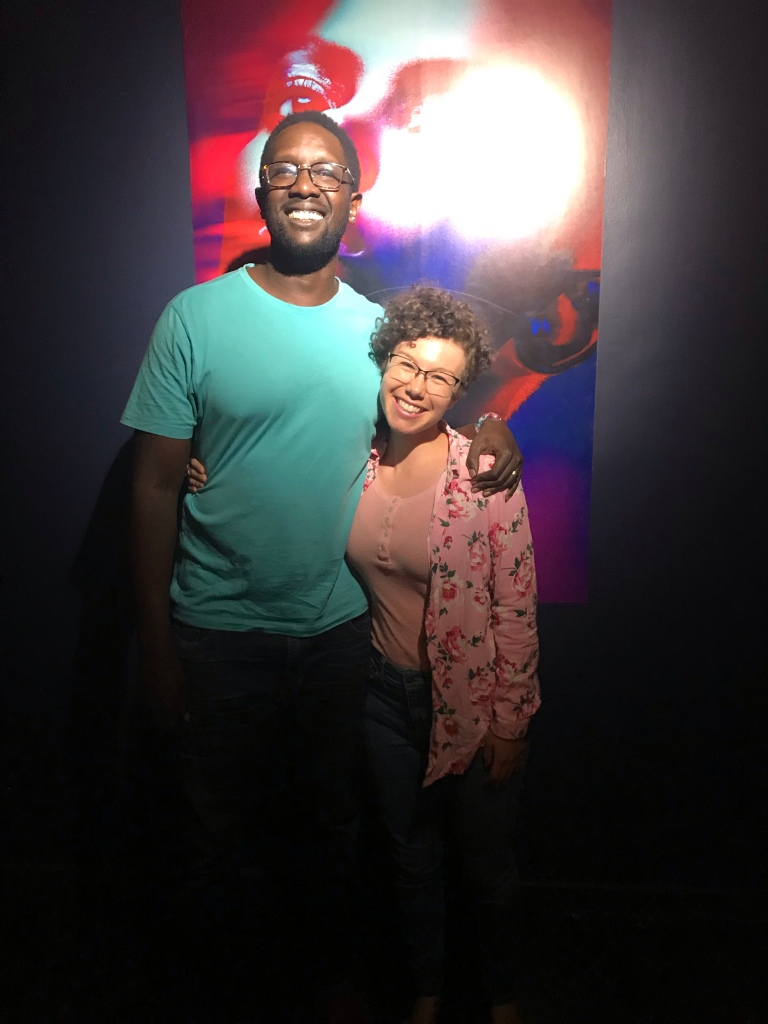 A tall Black man in a light teal shirt and square glasses smiles into the light with his arm around a short white woman with brown curly hair, a pink flowery shirt, and glasses. It is Tetu Shani and the author of this post.
