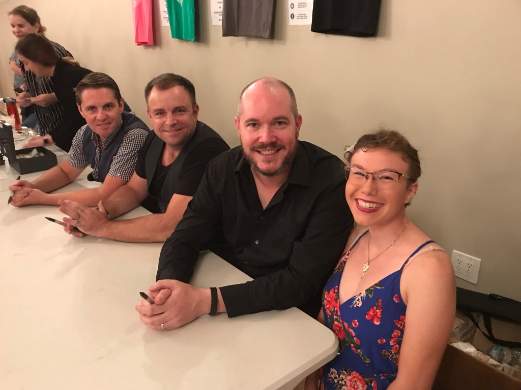 Three middle aged white men clasp their hands and smile behind a table. They are the High Kings. A young woman in a blue flowery dress, the author of this post, beams beside them.